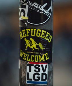 Urban street art sticker on a post displays 'refugees welcome'