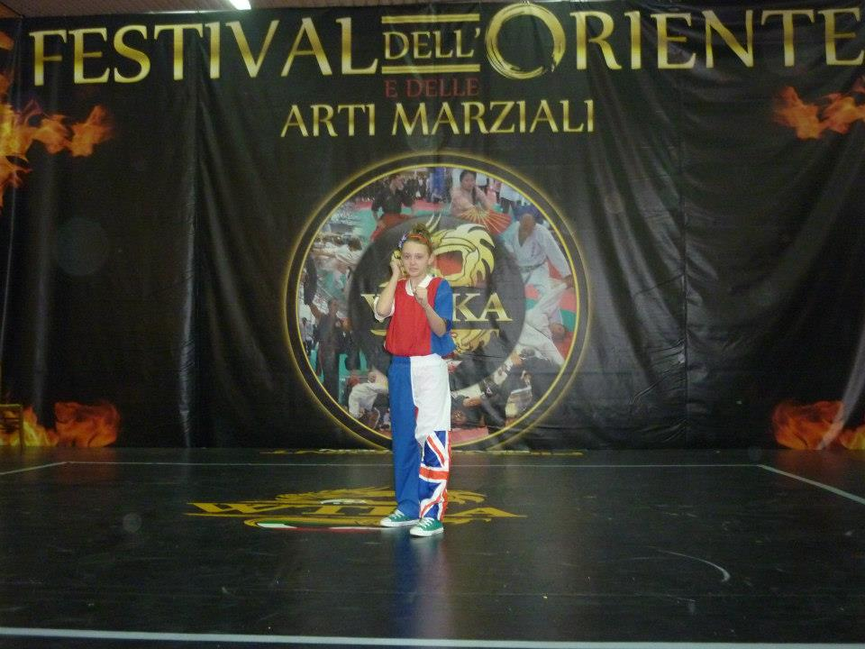 Girl standing on stage in front of banner that reads 'Festival dell' Oriente e delle arti marziali'