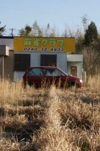 A car sits abandoned surrounded by overgrown weeds in Fukushima Prefecture