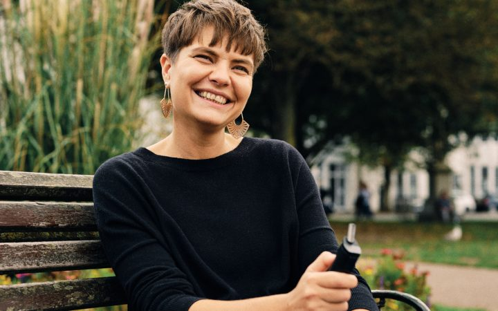 Woman smiles while sat on park bench