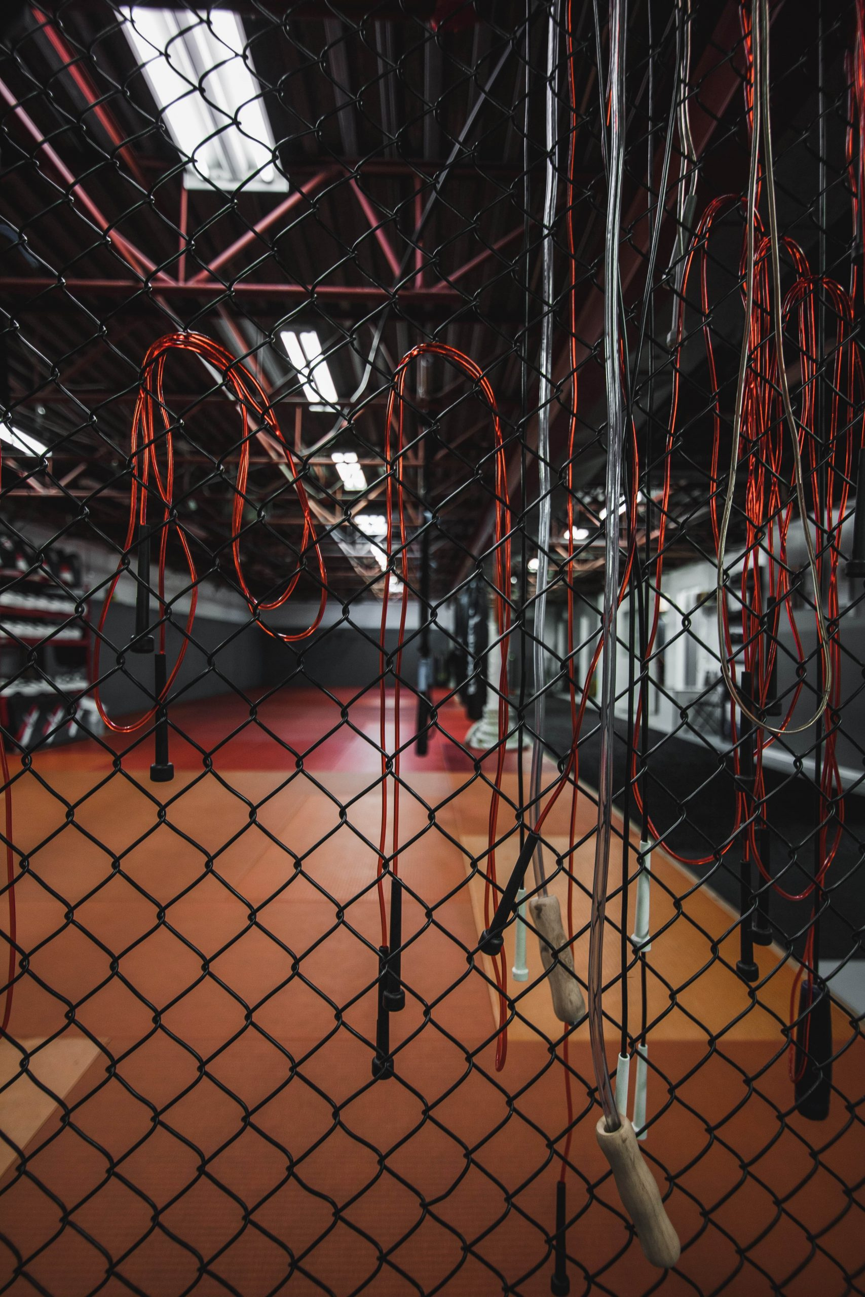 white and red skipping ropes hanging on chain link gate in gym