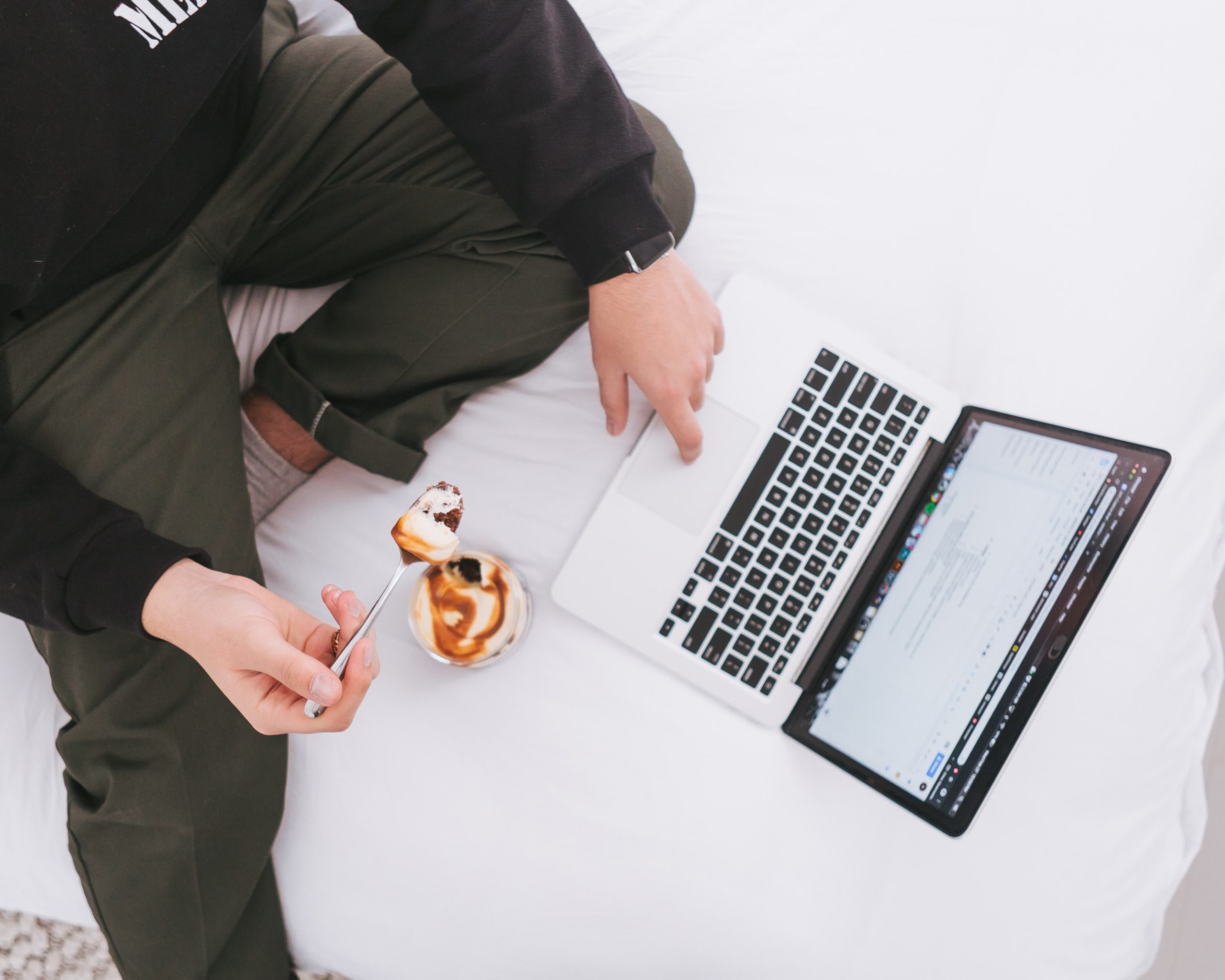 Mac laptop on white sheets, someone taps the keypad and simultaneously eats a pastry.- https://unsplash.com/photos/rem8NLYE2Jo image free from Unsplash