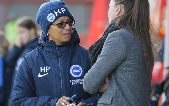 Hope Powell talking to a woman during a football match, wearing the team's coat and beanie