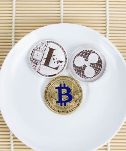 Two forks and a plate with crypto currency tokens on it.