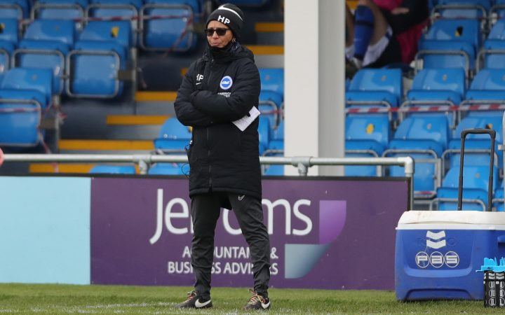 Hope Powell watching football match from the sidelines, wearing Brighton and Hove Albion uniform