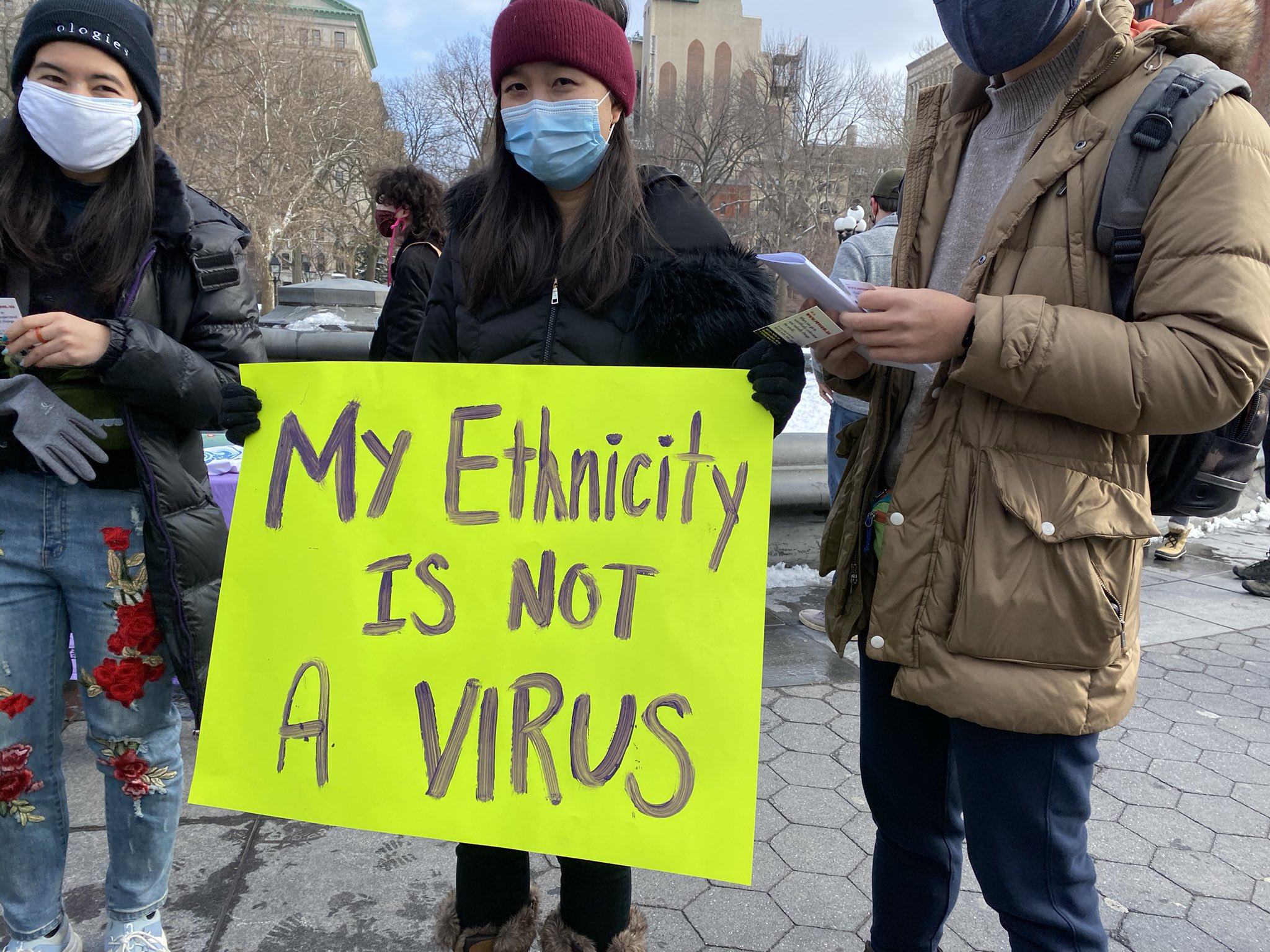 Protestors in New York City at the End Violence Against Asians rally with a banner reading 'My Ethnicity Is Not A Virus'