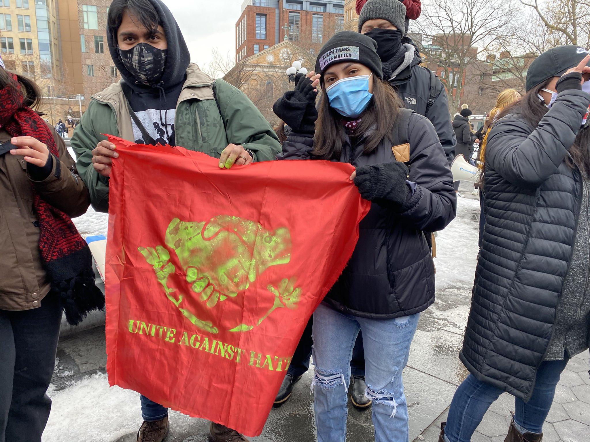 Protestors in Washington Sq Park hold a 'Unite Against Hate' flag.