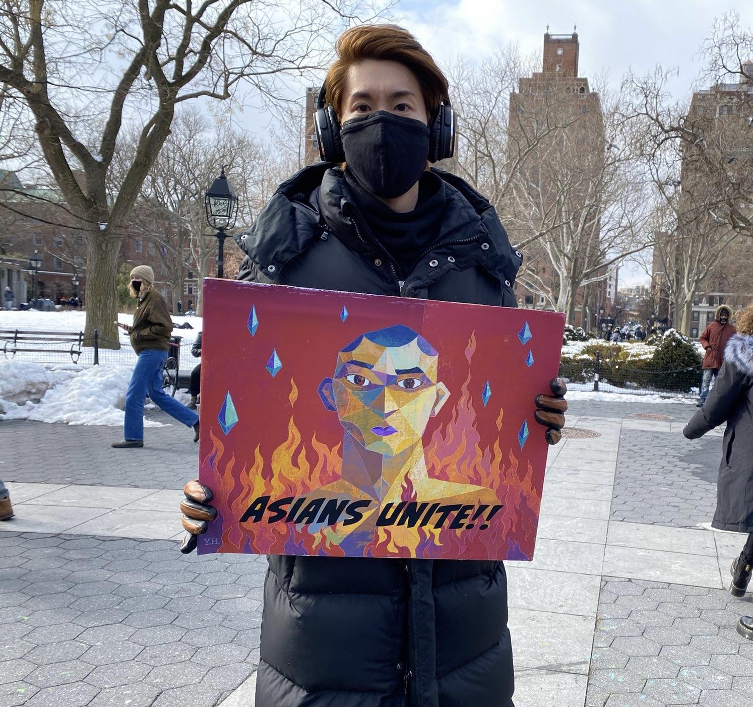 Protestor Yohey Horishita holding a painting with 'Asians Unite' across it.
