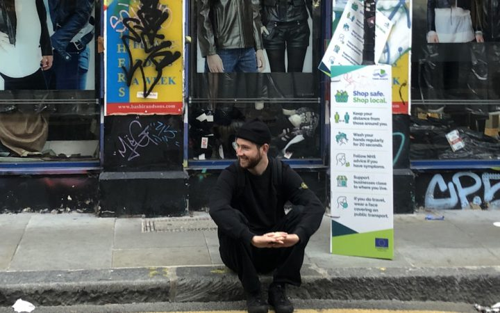 An image of Jarah sat on a pavement on Brick Lane in London
