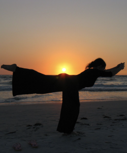 Person performing a yoga pose against the sunset. Photograph by Andrew Kalat
