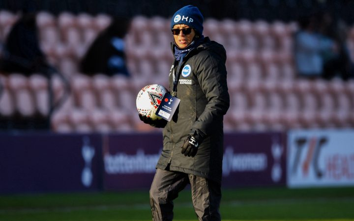 Hope Powell wearing a beanie and sunglasses at football match, holding a football