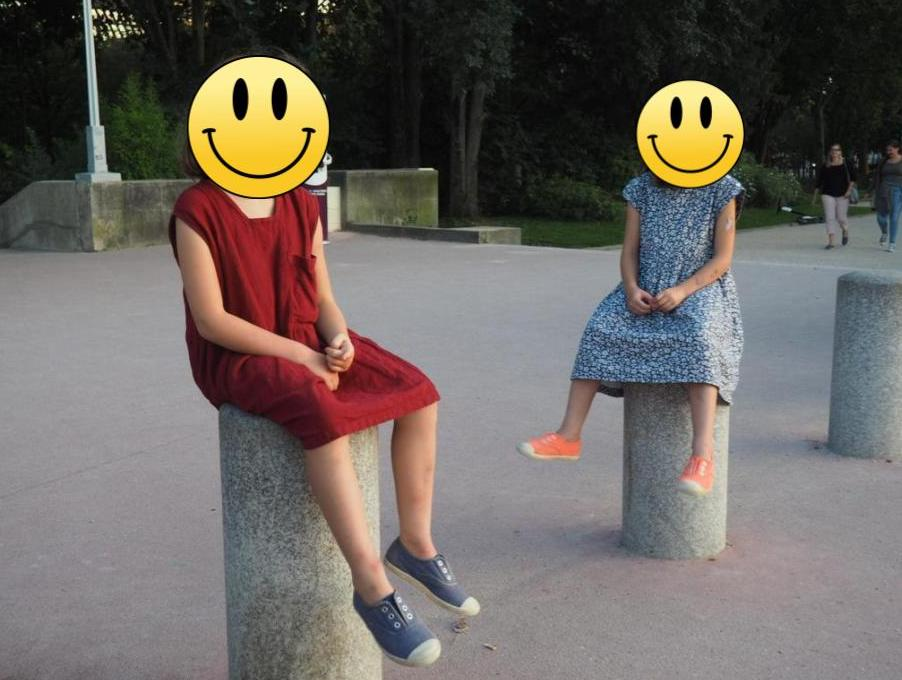 Image of two young girls edited with their faces covered by cartoon smiley faces