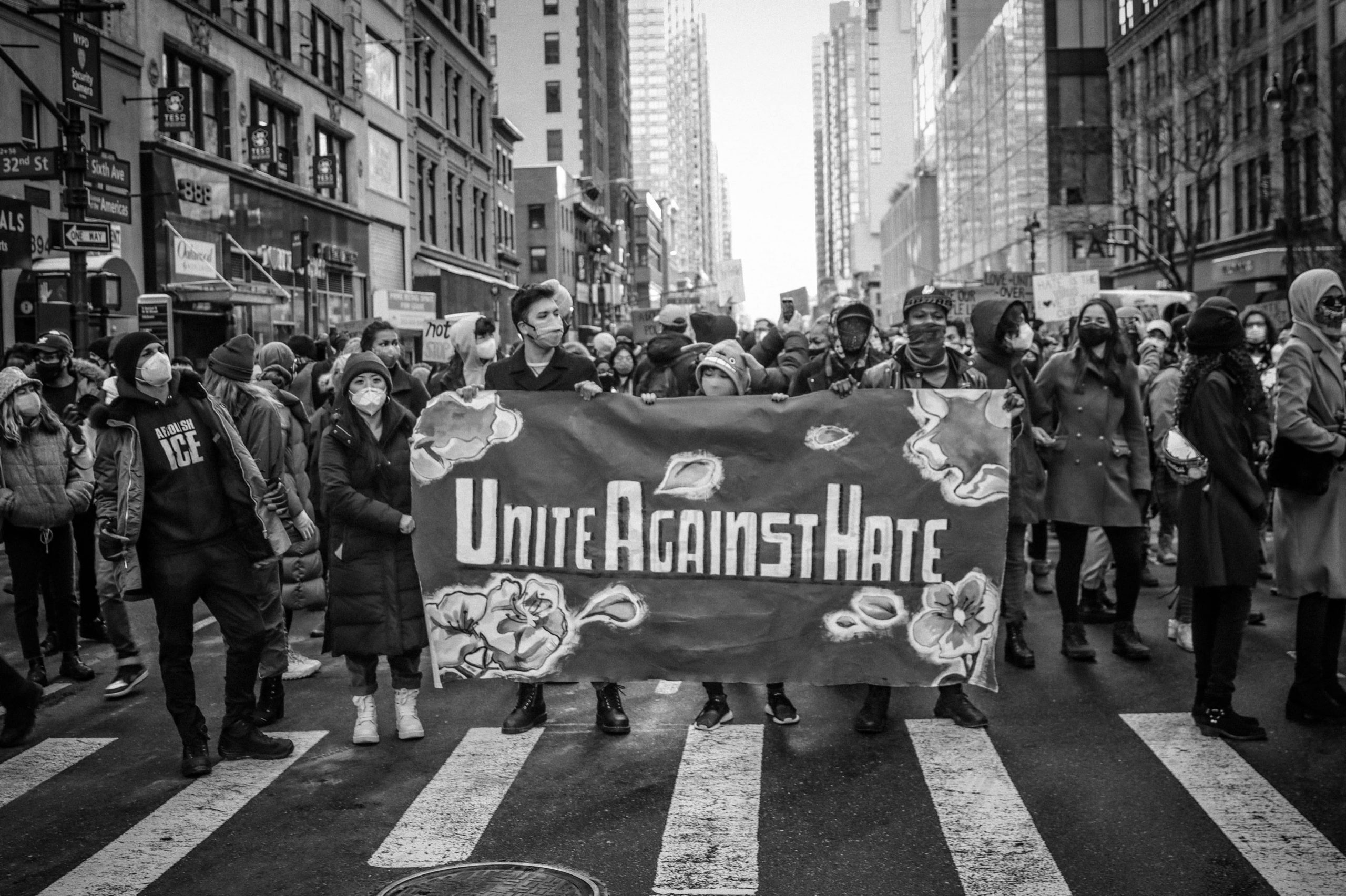 Protestors in New York City marching in the streets at the End Violence Against Asians rally. Four protestors carry a banner reading 'Unite Against Hate'