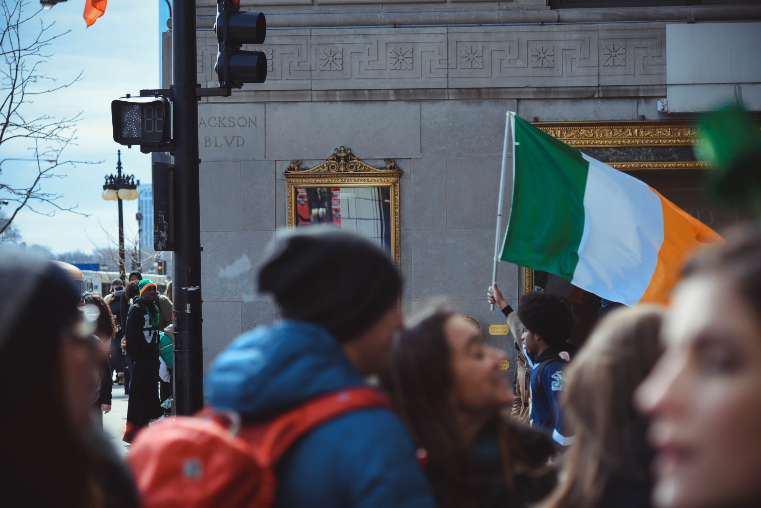 Crowd of people with Irish flag visible in background