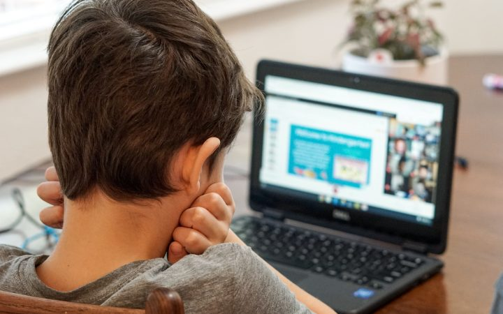 boy in grey shirt using black laptop for online learning