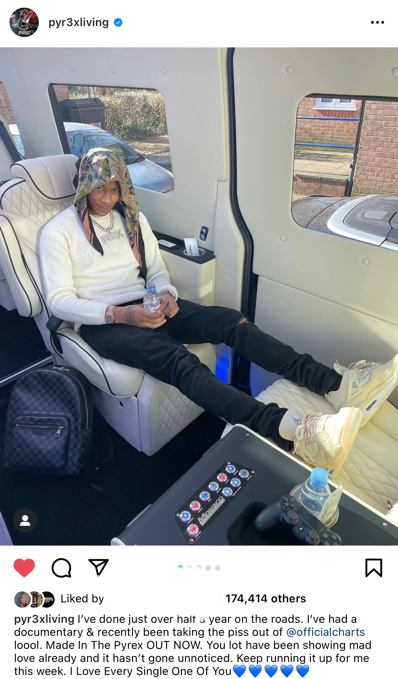 Screenshot of rapper, Digga D sitting with his feet up in the back of large car