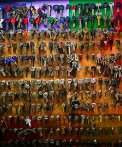 Hundreds of keys on a wall, with colourful background: purple, green, red, yellow and orange