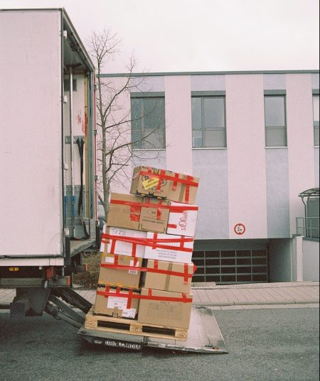 Moving houses, boxes closed with red tape outside movers' truck.