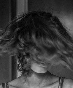 Black and white photo of woman swishing hair.