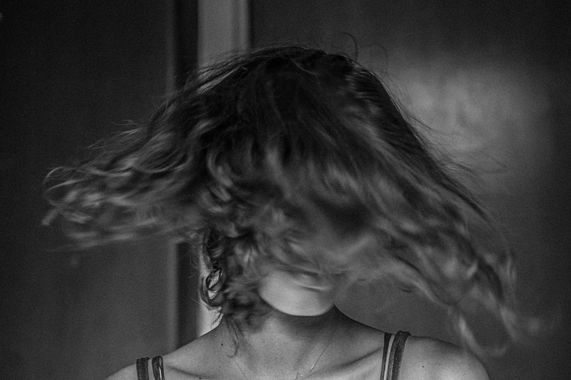 Black and white photo of woman swishing hair.