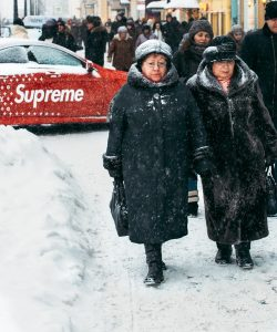 A Supreme x Louis Vuttion car and people walking down the street.